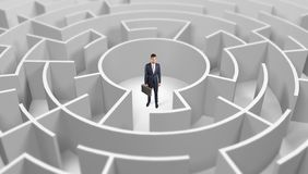 Businessman standing in a middle of a round maze stock photography