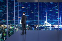 Technology and information concept. Businessman standing in minimalistic office interior with night New York city view and bog data on windows. Technology and royalty free stock photo
