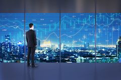 Trade and finance concept. Businessman standing in minimalistic office interior with night New York city view and forex chart on windows. Trade and finance stock images