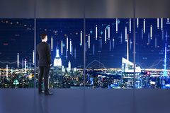Trade and stock concept. Businessman standing in minimalistic office interior with night New York city view and forex chart on windows. Trade and stock concept stock image