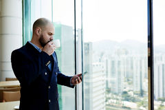 Businessman is standing in modern office interior near window with city view Royalty Free Stock Image