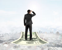 Businessman standing on money flying carpet watching the front Royalty Free Stock Photo