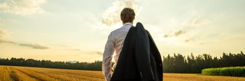 Businessman standing in nature under evening sky looking in to the distance with his suit jacket over his stock images