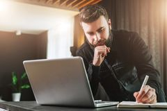 Businessman is standing near computer, working on laptop, making notes in notebook. Man watching webinar, learning. Young bearded businessman in black shirt is royalty free stock photo