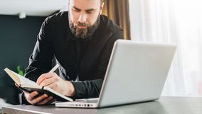 Businessman is standing near computer, working on laptop, making notes in notebook. Man watching webinar, learning. Young bearded businessman in black shirt is stock photography