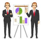 Businessman standing near flip board pointing and explaining finances concept Royalty Free Stock Images