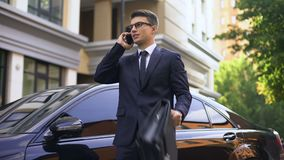 Businessman standing near luxurious car talking on smartphone, unhappy with news stock video footage