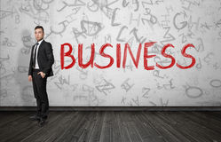 Businessman standing near red word 'Business'. Stock Image