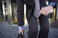 Businessman standing near revolving door, picking up briefcase, front view, mid-section Royalty Free Stock Photos