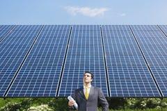 Businessman standing near solar panels Stock Photo