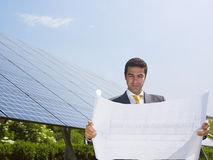Businessman standing near solar panels Stock Photo