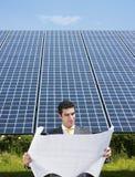 Businessman standing near solar panels Stock Images
