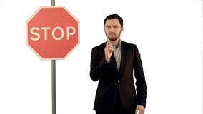 Businessman standing near a stop sign on laptop on white background isolated. Professional shot on BMCC RAW with high dynamic range. You can use it e.g in Royalty Free Stock Image