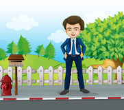 A businessman standing near the wooden mailbox Stock Image