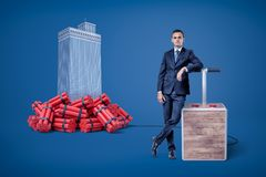 Businessman standing next to detonator box connected to heap of dynamite beside high-rise building in the background. Businesspeople rule cities. Play stock images