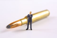 Businessman standing next to rifle round Stock Photo