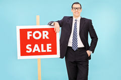 Businessman standing next to a for sale sign Royalty Free Stock Images