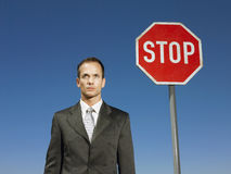 Businessman Standing Next To Stop Sign Stock Image