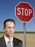 Businessman Standing Next To Stop Sign Stock Photography