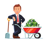 Businessman standing next to wheelbarrow with cash. Businessman standing leaning on the shovel next to wheelbarrow full of strapped cash dollar banknote bundles Royalty Free Stock Photography