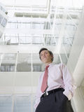 Businessman Standing In Office Atrium Stock Photo