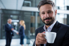 Businessman standing in office corridor with coffee cup Stock Image