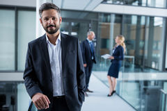 Businessman standing in office corridor and colleagues talking in background Stock Photos
