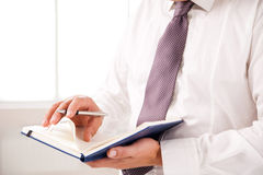 Businessman standing in office holding diary Stock Images