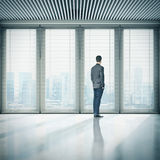 Businessman standing in office and looking at megalopolis Royalty Free Stock Images