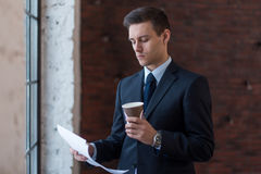 Businessman standing in office reading documents and drinking coffee. Royalty Free Stock Images