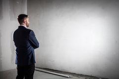 Businessman standing in an open empty space indoors and looking at the wall. Royalty Free Stock Photo