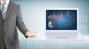 Businessman standing with open laptop. Businessman with open laptop. High-tech graphs at backdrop Stock Image