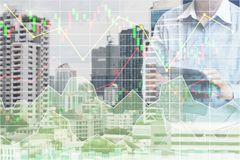 Businessman  standing and operate tablet to control and connect. Big data of real estate sector stock market index with chart and graph background Stock Images