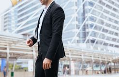 Businessman standing outdoor in city,Lifestyle with positive attitude expressing energy in good time. Cropped image royalty free stock images