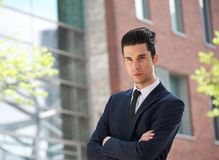 Businessman standing outdoors with arms crossed Stock Photo