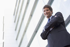 Businessman standing outdoors by building smiling Stock Photo
