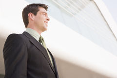 Businessman standing outdoors by building smiling Stock Photos