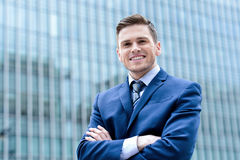 Businessman standing at outdoors. Confident businessman posing with folded arms outside skyscraper royalty free stock photo