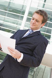 Businessman standing outdoors looking at paperwork Royalty Free Stock Photos