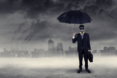 Businessman standing outdoors under air pollution Royalty Free Stock Photo