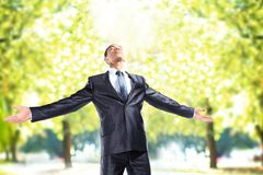 Businessman standing outside with arms outstretched Stock Image