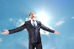 Businessman standing outside with arms outstretched Royalty Free Stock Image