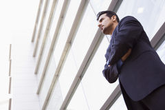 Businessman standing outside modern office. Building Stock Image
