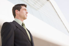 Businessman standing outside office. Looking off camera royalty free stock images