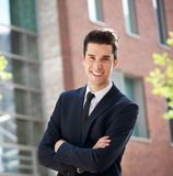 Businessman standing outside the office with arms crossed Stock Photos
