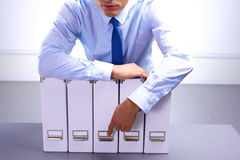 Businessman standing over a folder with documents royalty free stock images
