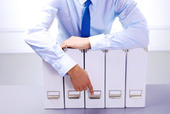 Businessman standing over a folder with documents stock photo