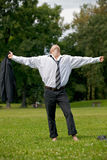 Businessman standing in park with arms outstretched Royalty Free Stock Images