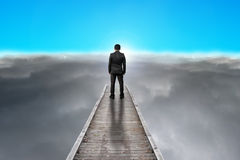 Businessman standing on pier looking sunrise with clouds, blue s Stock Photo