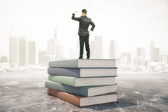 Businessman standing on a pile of books, learning concept Stock Images
